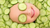 pepinos : Smiling womans face surrounded by cucumber slices and covering her eyes