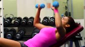 Sporty young woman lifting dumbbells while lying on exercising device