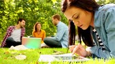 campus : Cute young woman using her tablet while lying on a lawn wit her friends