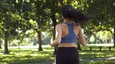 Brunette running in park in slow motion Wideo