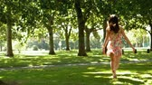 długi : Attractive brunette bouncing through park in slow motion