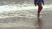 Female legs walking at the beach in slow motion