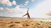 jumping : Woman doing cartwheel at the beach in slow motion