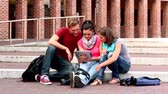 passos : Happy students using tablet outside on steps in college