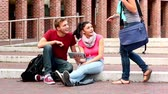 campus : Happy students using tablet pc outside on steps in college Stock Footage