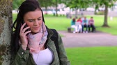 aborrecido : Annoyed student leaning against a tree making a phone call on college campus Stock Footage