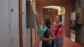cabelo castanho : Two students walking down hallway to locker in college Vídeos