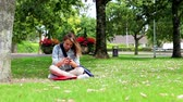 campus : Student sitting on the grass making a phone call in college campus Stock Footage