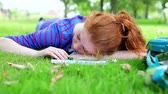 вдумчивый : Pretty young student lying on the grass studying on college campus