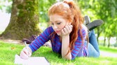 caneta : Pretty young student lying on the grass making notes  on college campus