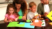 dobrável : Parents and children making paper shapes together at the table in slow motion Vídeos