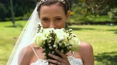 cabelo castanho : Bride smelling her bouquet in the park in slow motion Vídeos