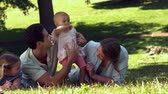 высокоскоростной : Young family relaxing in the park together in slow motion