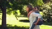 высокоскоростной : Young mother giving her daughter a piggy back in the park in slow motion