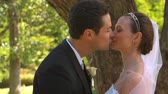 жена : Newlyweds kissing in the park in slow motion
