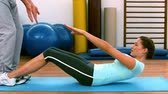 físico : Woman doing sit ups with her trainer in slow motion