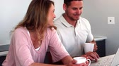 высокоскоростной : Happy couple having coffee and using laptop in kitchen in slow motion