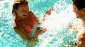 closeness : Sexy couple splashing in the pool together on holidays in slow motion