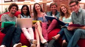 comum : Happy students smiling at camera in common room in slow motion Stock Footage