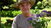 arbusto : Retired man gardening and smiling at camera at home in the garden