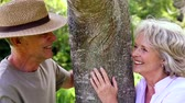 tronco : Retired couple leaning against tree smiling at each other at home in the garden Vídeos