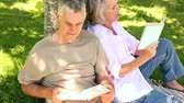 tronco : Retired couple leaning against tree reading at home in the garden Vídeos