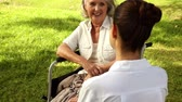 prato : Nurse talking to woman in wheelchair outside on a sunny day Stock Footage