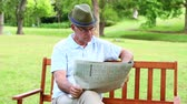 thinking : Retired man reading the paper on a park bench on a sunny day