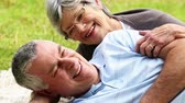 prato : Affectionate senior couple relaxing in the park lying on blanket on a sunny day