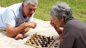 chess board : Senior couple relaxing in the park lying on a blanket playing chess on a sunny day