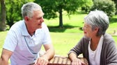 пенсионер : Happy senior couple relaxing in the park with a picnic basket on a sunny day