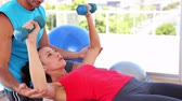 desportivo : Fit woman lifting dumbbells on blue exercise ball with trainer at the gym Stock Footage