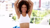 instrutor : Fit woman standing in tree pose smiling at camera at the gym Stock Footage