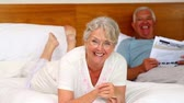 jornal : Senior couple relaxing on bed at home in the bedroom