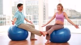 instrutor : Pregnant woman doing yoga with a personal trainer in a fitness studio Stock Footage