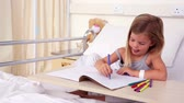 treatment : Little girl sitting in hospital bed colouring in the hospital ward