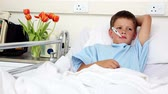 gripe : Little sick boy sitting in bed with thermometer in the hospital ward