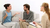writing : Young couple arguing while therapist takes notes at therapy session Stock Footage