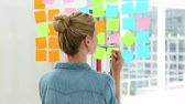 thinking : Blonde designer looking at post its on window in creative office