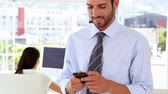 discagem : Man texting on phone while colleague works behind him in the office Stock Footage