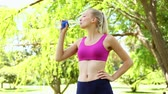 desportivo : Fit blonde drinking water in the park on a sunny day
