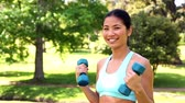 físico : Fit asian girl lifting dumbbells on a sunny day