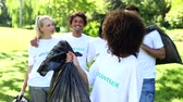 bem estar : Happy volunteers picking up trash in the park on a sunny day