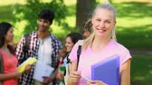 выше : Student smiling at camera with friends standing behind her on a sunny day