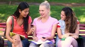 выше : Students chatting together outside on a bench on a sunny day