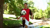 chutando : Girl playing football in the park in slow motion Stock Footage