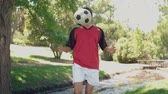 pontapé : Asian girl playing football in the park in slow motion Stock Footage