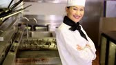 ok : Happy chef smiling at camera beside the stove in commercial kitchen