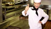 laço : Happy chef smiling at camera beside the stove in commercial kitchen
