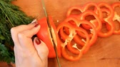 vegetarianismo : female hand slices a red sweet pepper with a green knife on a wooden board